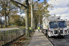 Hurricane Sandy. Sanitation workers  are cleaning up the sidewalk after the Hurricane Sandy in Middle Village, Quens, New York Stock Photo