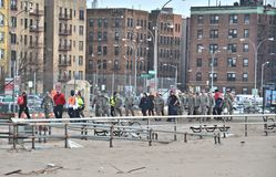 Hurricane Sandy's Aftermath. Members of the National Guard and volunteers walking down on Riegelmann Boardwalk in Brighton Beach, Brooklyn, after Hurricane Sandy Stock Photo
