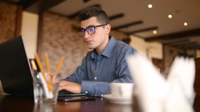 Hurried handsome young male businessman in glasses working under pressure on laptop, many wireless communication devices. Responding to mail messages and stock video