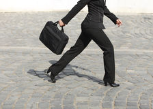 Hurry. Businesswoman's legs, as she is walking in a hurry along a cobbled street Royalty Free Stock Photos