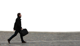 Hurry. Young businessman walking along a cobbled street in front of a white wall Royalty Free Stock Photography
