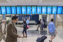 In a hurry at the airport. ATLANTA, USA - OCTOBER 14, 2014: Flight status monitors hang from the ceiling in the Atllanta International Airport as travelers hurry Royalty Free Stock Photo