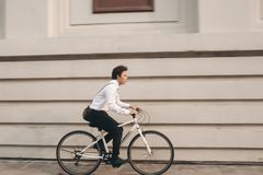 Hurry Asian businessman riding bike in rush hour.  Young man lat. E for train work, meeting. Office life and business competition Stock Photography