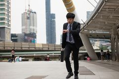 Hurry Asian businessman run and check time. Hurry Asian businessman running and looking at watch to check time on city walk in rush hour. Young man late for Royalty Free Stock Photography