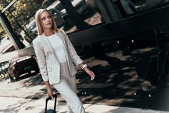 In a hurry. Beautiful young woman in suit pulling luggage while walking outdoors stock photography