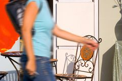 In a hurry - Blurred concept. Girl in a hurry moving by outdoor cafe Stock Photography