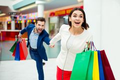 Hurry faster! It`s shopping time and fun. Handsome cheerful  suc. Cessful happy  men  holding hands and following his lovely cute women with colored shopping Stock Image