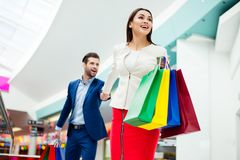 Hurry faster! It`s shopping time and fun. Handsome cheerful  suc. Cessful happy  men  holding hands and following his lovely cute women with colored shopping Royalty Free Stock Photos