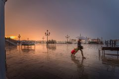 a girl in a hurry on rainy early morning with suitcase stock photo