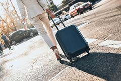 In a hurry. Close up rear view of young woman pulling luggage while walking outdoors stock photography