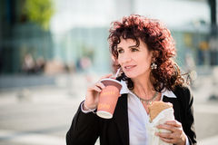 Hurry life - business woman eating in street Stock Image