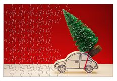 Hurry up! Christmas is coming! Holiday concept with a small pine tree on handmade cartoon toy car in jigsaw puzzle shape.  royalty free stock photo