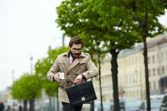 Hurry up. Contemporary businessman moving along street and looking at watch stock image