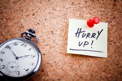 Hurry up. ! written on a post note and hanged on the cork-board with an old pocket watch Royalty Free Stock Photo