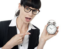 Hurry up! You are late for the meeting. Amazed female executive pointing at time. You are late for the meeting Stock Images
