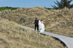 In Hurry for the Wedding. After the photo session on the beach the young couple walks briskly between the dunes, the bride holding her bridal gown high Stock Photography