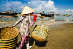 In a hurry. The woman worker wearing conical hat is in a hurry. She's carrying empty baskets back to the ships for new rounds of fish at Long Hai fish market Royalty Free Stock Photography