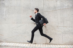 Hurrying to the new goals. Happy young man in formalwear holding briefcase while running in front of the concrete wall Stock Image