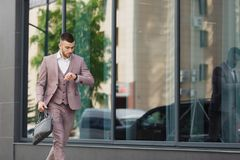 Young businessman with a briefcase running in a city street on a background of wall Stock Photos