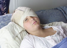 Hurt Girl In Bed. Young girl wearing bandage around her head. Hurt and sad, in recovery stock photography