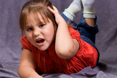 Hurt Head. A four year old girl holding her head in pain Royalty Free Stock Photos