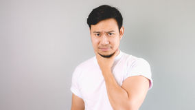 Hurt his throat because of caughing. An asian man with white t-shirt and grey background stock photography