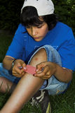 Hurt knee. Boy putting band-aid on his knee Royalty Free Stock Image