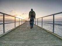 Hurt man with hooded jacket and forearm crutches looking sadly. Into sea water. Traveler stand on sea bridge within morning and thinking. Nostalgic silhouette royalty free stock photography