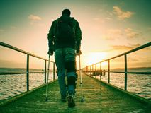 Hurt man with hooded jacket and forearm crutches  standing on sea bridge. Within  early morning and thinking. Gloomy nostalgic silhouette of sad lonely Stock Image