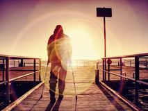 Hurt man with hooded jacket and forearm crutches  standing on sea bridge. Within  early morning and thinking. Gloomy nostalgic silhouette of sad lonely Royalty Free Stock Photo