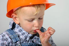 Hurt my finger. Cute toddler boy with hard hat putting a hurt finger in his mouth royalty free stock images