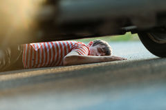 Hurt and unconscious child on asphalt Royalty Free Stock Image
