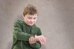 Hurt Wrist. Boy in Pain Holding His Wrist stock photos