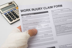 Work injury claim form. Hurted hand holding a work injury claim form Royalty Free Stock Photos