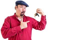 Hurtig stolt stor man som pekar till hans biltangenter Fotografering för Bildbyråer