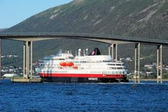 Tromso - Hurtigruten under the Tromso bridge  - cruise service along Norways coast Royalty Free Stock Photo