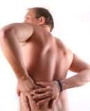 Hurting Back. A young man is holding his back in pain Stock Photo
