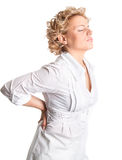 Hurting back pain. Young woman holds her back in pain Stock Photo