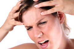 Hurting head. A young woman is holding her head in pain Stock Image
