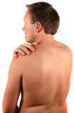 Hurting Pain In The Shoulder. A young man is holding his shoulder in pain Stock Photo