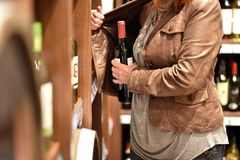 Hurto en el supermercado - la mujer roba una botella de vino rojo imagenes de archivo
