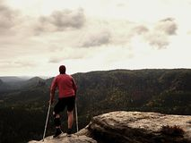 Hurts hiker with knee brace features. Man with leg in join immobilizer stay on summit and take a rest Stock Photography