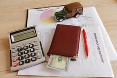 Husägare- och bilförsäkring bildar med bärbara datorn, skrivaren, pennan, dollar, räknemaskin på tabellen Royaltyfri Foto