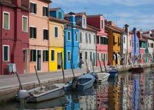 Hus av Burano och reflexionen i vattnet Vattenvägar med traditionella fartyg och den färgrika fasaden arkivbilder