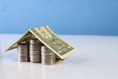 Hus av dollarsedeln på staplade mynt Arkivfoton