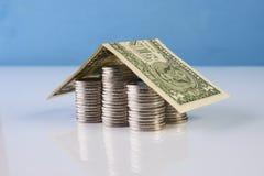 Hus av dollarsedeln på staplade mynt Royaltyfria Bilder