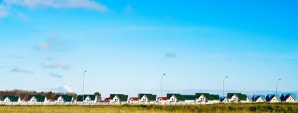 Hus av olika färger och blå himmel Arkivbild
