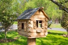 Hus av trästänger med Windows som en fågelförlagematare royaltyfri foto