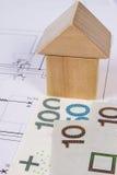 Hus av träkvarter och polsk valuta på byggnadsritningen, byggande husbegrepp Arkivfoto
