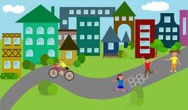 Hus en liten stad, barnlek på vägen, höghus Arkivbilder